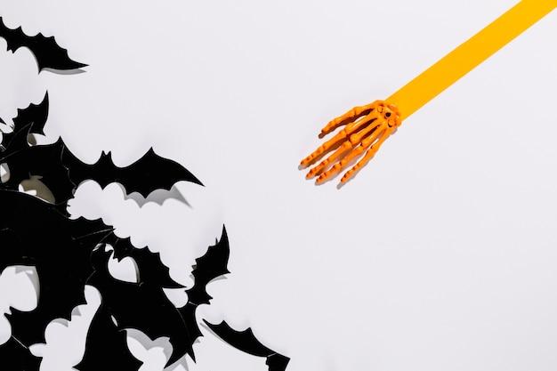 Morcegos decorativos de halloween perto da mão de esqueleto