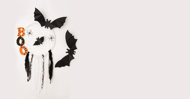 Morcegos e um apanhador de sonhos em um fundo branco são um conceito de halloween.