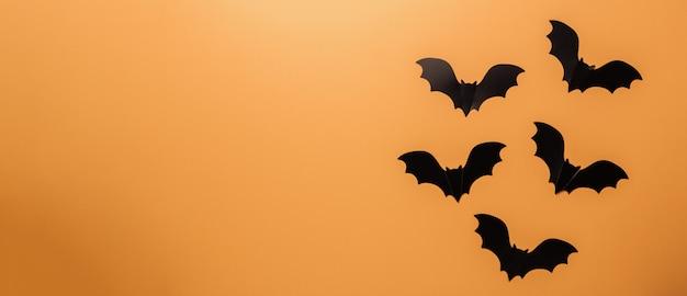 Morcegos pretos em fundo laranja
