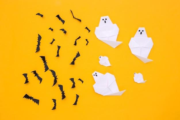 Morcegos voadores de papel, fantasmas em fundo amarelo. fundo feito à mão de halloween. vista do topo. postura plana