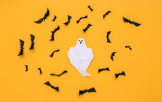 Morcegos voando de papel, fantasma em fundo amarelo. fundo de dia das bruxas. vista do topo. postura plana