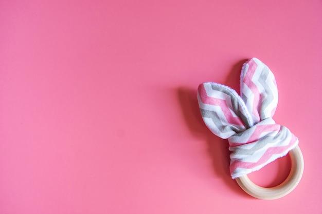 Mordedor de coelho de bebê fofo orgânico no fundo rosa com espaço de cópia.
