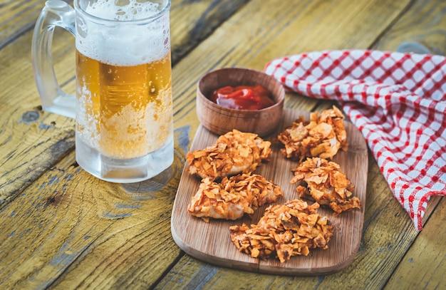 Mordidas de frango de churrasco com caneca de cerveja
