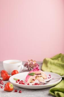 Mordido bolo mousse rosa com morango e uma xícara de café em uma superfície de concreto cinza. vista lateral, foco seletivo, cópia espaço.
