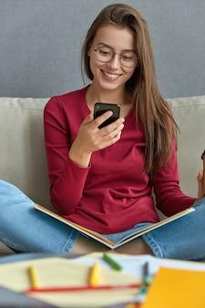 Morena adorável satisfeita atualiza perfil nas redes sociais, segura telefone, instala app no celular digital, senta pernas cruzadas no sofá com livro nas pernas, mesa com papéis, canetas em primeiro plano