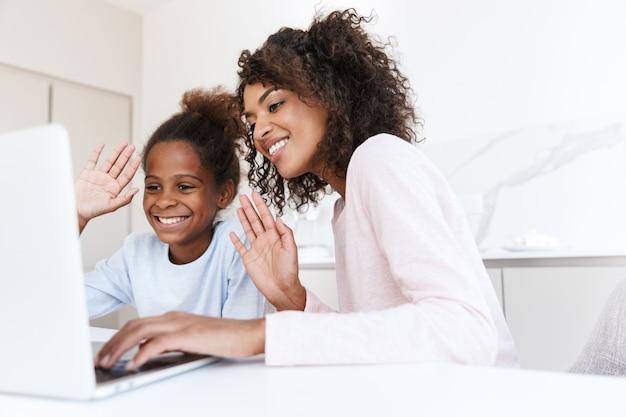 Morena afro-americana e sua filha usando o laptop em casa