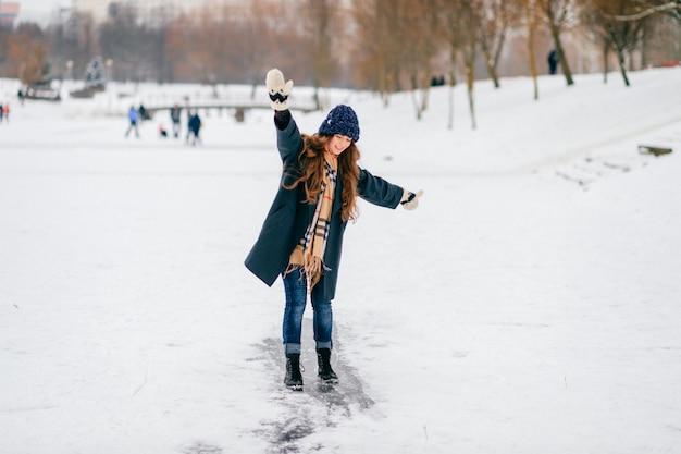 Morena alegre de cabelos compridos feliz que monta a trilha do gelo no lago congelado no dia de inverno.