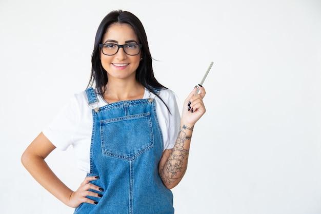Morena alegre de óculos, segurando a caneta na mão levantada