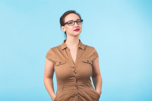 Morena alegre elegante em óculos, sorrindo para a câmera em um fundo azul com espaço de cópia