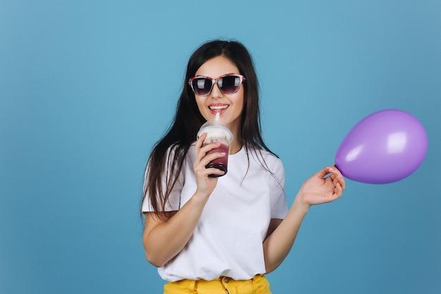 Morena alegre em óculos de sol pretos parece feliz posando com um coquetel e balão