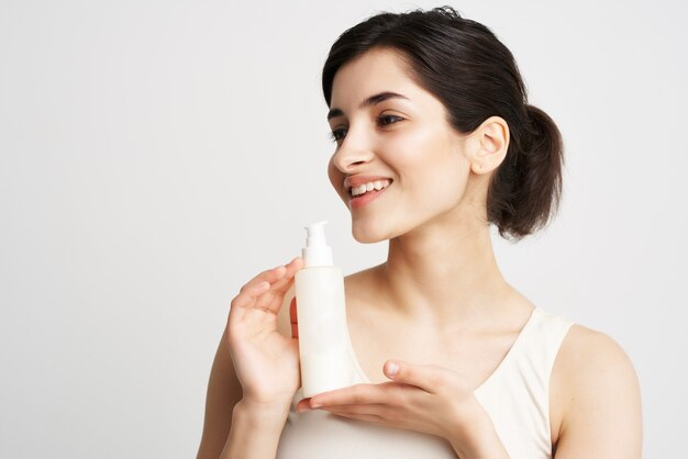 Morena alegre em uma camiseta branca cosmetologia pele limpa