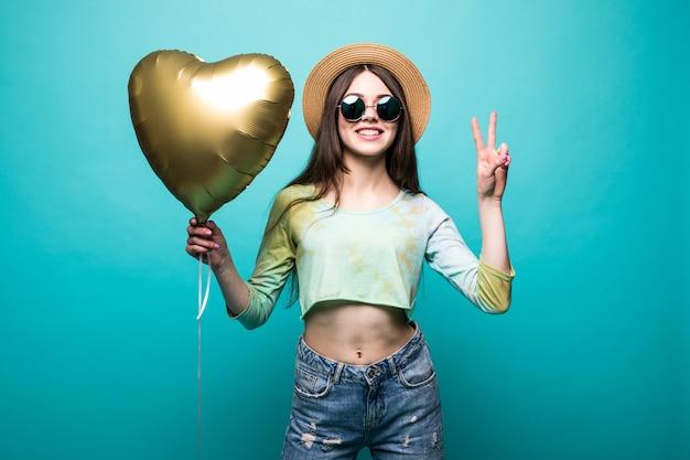 Morena alegre linda senhora vestida segurando um balão de ar dourado como coração e mostrando gesto de paz isolado
