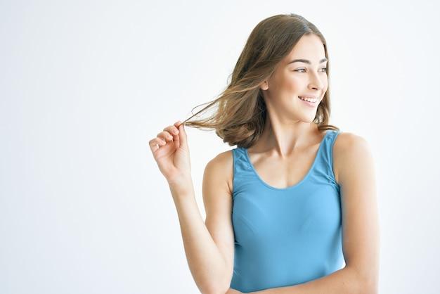 Morena alegre perto da janela posando em estúdio de penteado da moda