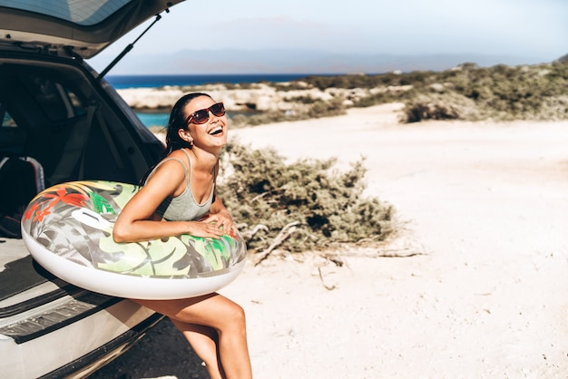 Morena asiática da bandeja bonita com o flutuador perto do tronco de carro na praia do beira-mar.