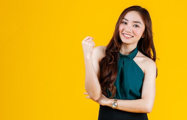 Morena asiática feminina de cabelos cacheados fofo e charmoso dos anos 30 posar para a câmera com um gesto alegre e positivo para fins publicitários. tirada com flash de estúdio isolado em fundo amarelo.