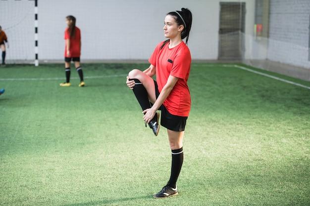 Morena ativa com uniforme esportivo se exercitando no campo de futebol com outras garotas jogando