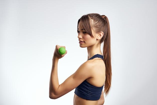 Morena atlética com halteres nas mãos treino vista recortada de fitness
