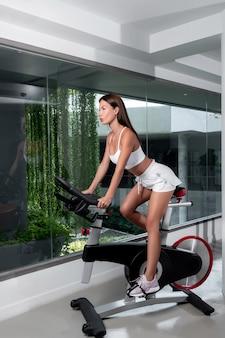 Morena atlética em um top branco e shorts curtos brancos posando enquanto está sentado em uma bicicleta ergométrica