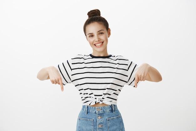 Morena atraente alegre sorrindo amplamente, apontando o dedo para baixo