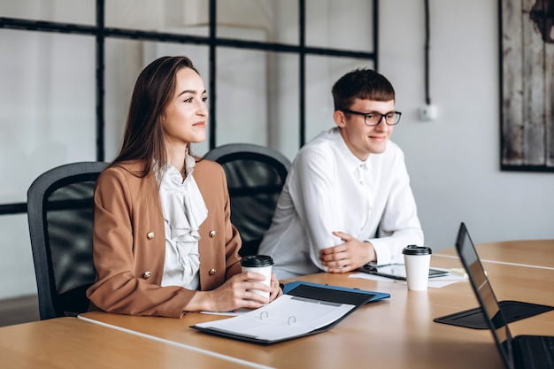 Morena atraente, bebendo café, seu colega de óculos ouve atentamente a reunião.