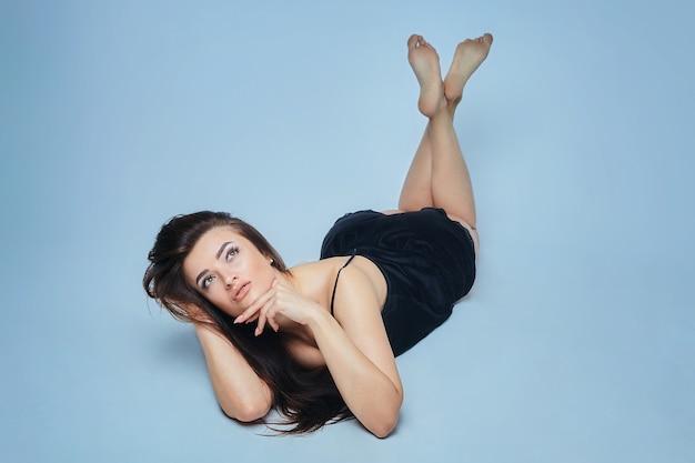 Morena atraente com as pernas cruzadas deitada, posando no estúdio em um fundo azul
