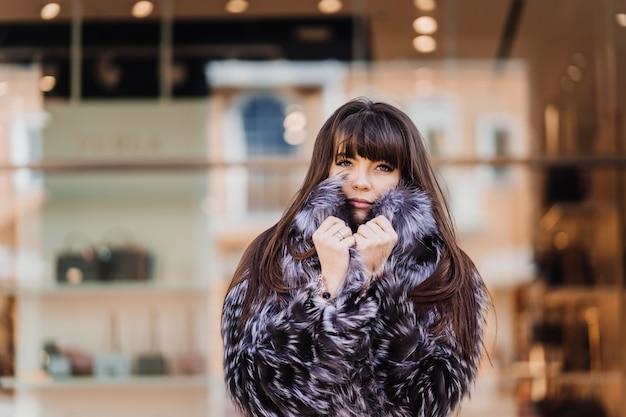 Morena atraente, com cabelos longos e lisos, vestindo um casaco de pele cinza, posando contra a construção