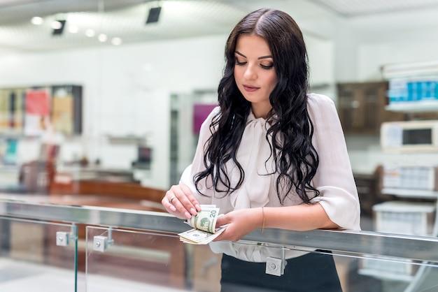 Morena atraente com notas de dólar em grande shopping