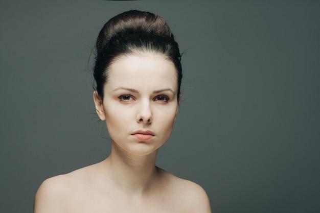 Morena atraente com ombros nus, pele clara e cinza