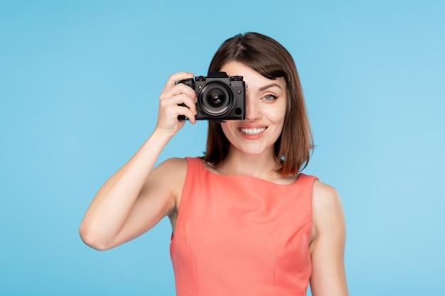 Morena atraente em um elegante vestido vermelho segurando a câmera pelo olho enquanto tira fotos na festa