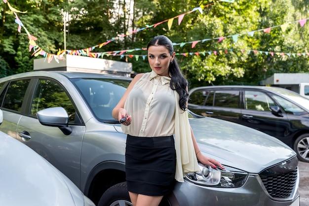 Morena atraente oferecendo a chave do carro novo