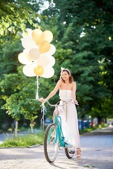 Morena atrativa de sorriso que guarda ballons ao conduzir a bicicleta azul na aleia do parque.
