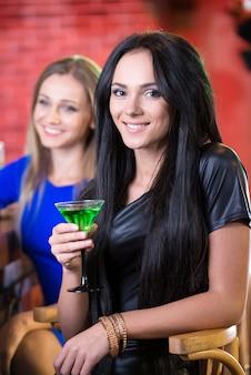 Morena bebendo um cocktail e sorrindo para a câmera.