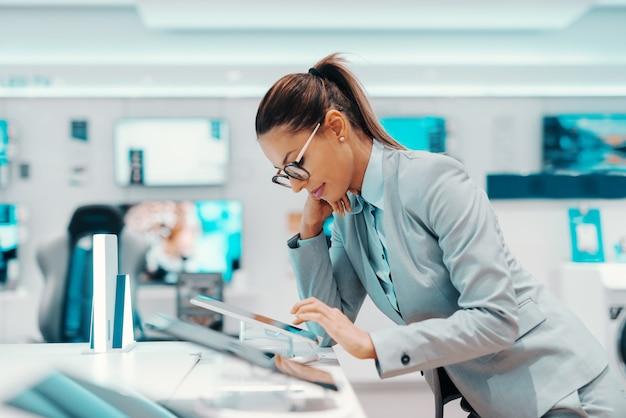 Morena bonita caucasiana com rabo de cavalo, vestida com roupa formal e com óculos, apoiando-se no balcão e experimentando o tablet. interior da loja de tecnologia.