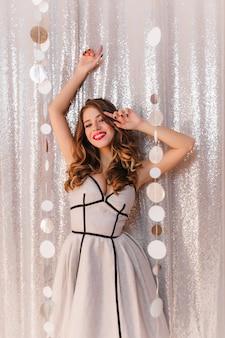 Morena bonita com cachos de hollywood em um vestido de cocktail prateado em uma festa festiva. menina sorrindo na parede de purpurina