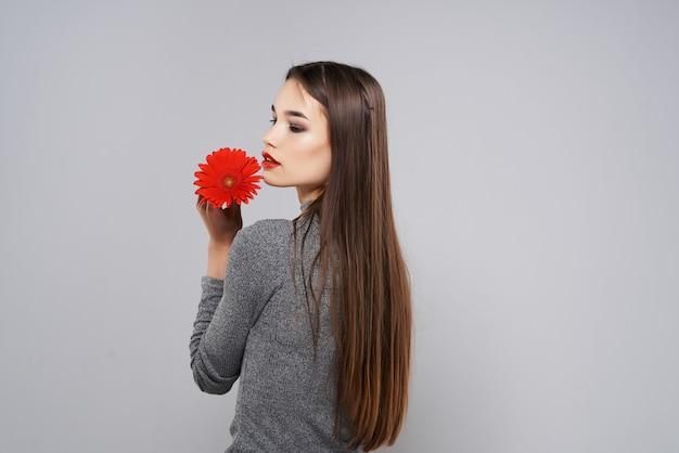 Morena bonita com modelo de maquiagem brilhante de flor vermelha