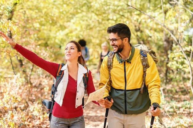 Morena bonita de sorriso que guarda o mapa, mostrando o caminho certo e conduzindo o resto dos caminhantes. ao lado dela, andando barbudo homem sorridente com óculos. floresta no exterior do outono.
