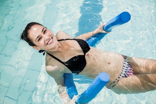 Morena bonita em traje de banho a nadar com um rolo de espuma na piscina