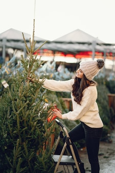 Morena bonita em uma camisola branca com árvore de natal