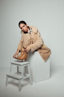 Morena bonita no outono roupas marrom botas nos acessórios da cadeira.