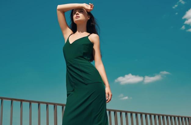Morena brilhante encantador em um vestido esmeralda