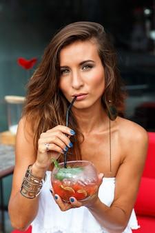 Morena bronzeada linda mulher relaxando e se divertindo no terraço do restaurante do hotel