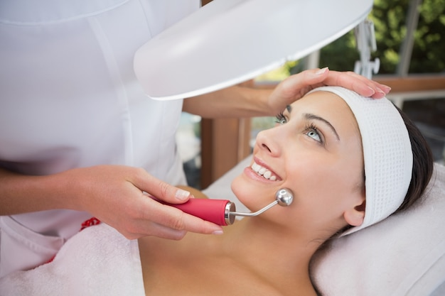 Morena calma recebendo micro dermabrasão de terapeuta de beleza