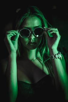 Morena caucasiana em um vestido preto iluminado por luz led verde refletida em cristais pretos. fotografia noturna urbana. mulher colocando óculos de sol