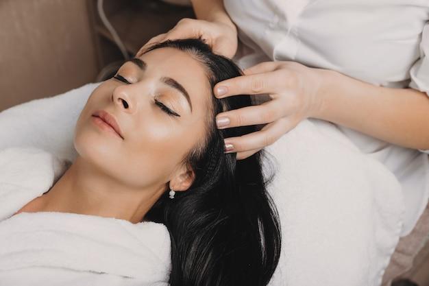 Morena caucasiana relaxada esperando de olhos fechados durante um procedimento de spa para sua pele e cabelo