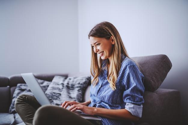 Morena caucasiano de sorriso atrativa nova que senta-se no sofá na sala de visitas e que usa o portátil para o trabalho autônomo.