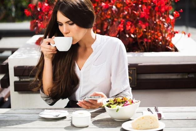 Morena com cabelo comprido bebe café à mesa Foto gratuita