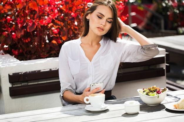 Morena com cabelo comprido bebe café à mesa