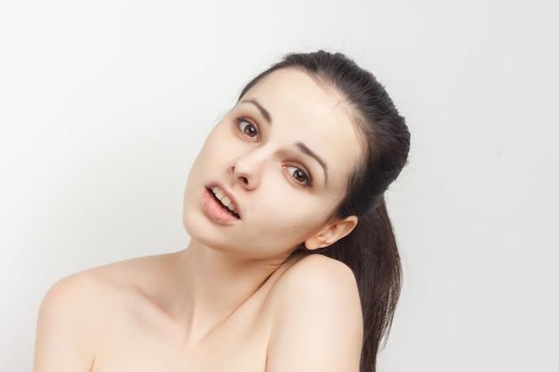 Morena com cabelo puxado e ombros nus com remoção de maquiagem