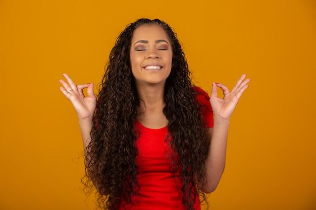 Morena com cabelos cacheados longos e brilhantes rezando