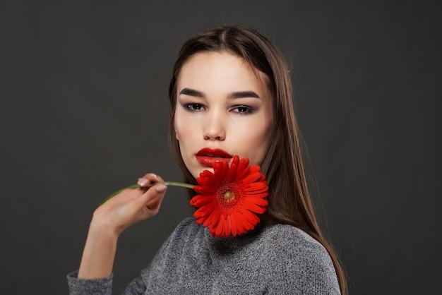 Morena com flor vermelha perto do rosto romance de cosméticos de luxo